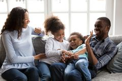 Happy black family laughing playing tickling children at home. Happy black family laughing playing with children at home, cheerful african american parents stock photos