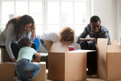 Happy black family with small kids unpack boxes royalty free stock images