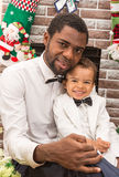 Happy black father and baby boy cuddling by fireplace. Christmas Royalty Free Stock Images
