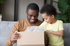 Happy black father and little kid son open cardboard box stock image
