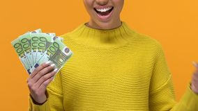 Happy black female pointing at euro banknotes in hand, financial success, salary. Stock footage stock video footage