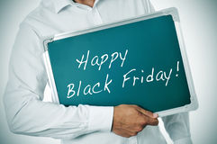 Happy black friday. A man showing a blackboard with the sentence happy black friday written in it royalty free stock image