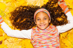 Happy black girl with curly hair in autumn leaves Royalty Free Stock Images