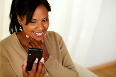 Happy black girl reading a message on mobile phone Royalty Free Stock Photography