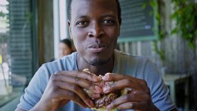 Happy black guy laugh and eats tasty meat burger. Hand held shot of a stylish black american man devouring and biting on a chewy enormous hamburger with two stock footage