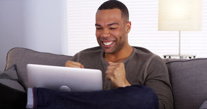 Happy Black guy streaming the game on his laptop stock image