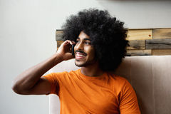 Happy black guy talking on mobile phone indoors Royalty Free Stock Photography