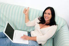 Woman using a laptop. Happy Black haired woman using a laptop Royalty Free Stock Photos
