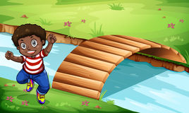 A happy Black kid near the wooden bridge Royalty Free Stock Photo