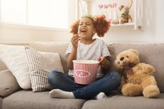 Laughing black little girl watching movie at home. Happy black little girl watching tv and eating popcorn at home. Candid portrait of laughing african-american Stock Photography