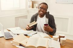 Happy black male student studying at table full of books. Happy african-american student studying at working table. Tired but still smiling male student Stock Photography