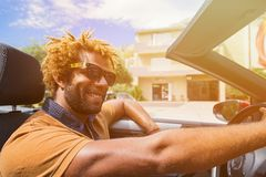 Happy black man driving a convertible car. Young happy black man with dread locks wearing sunglasses sitting in the convertible car. Sun effect applied royalty free stock photography