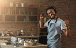 Happy black man listening to music and dancing in kitchen