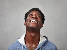 Happy black man. Happy smiling african american man gray wall background stock photo