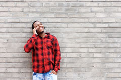 Happy black man talking on cell phone by wall Royalty Free Stock Image