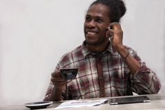 A Happy black man using smart phone at home. Smiling young african man at home sitting on couch while drinking coffee stock photos