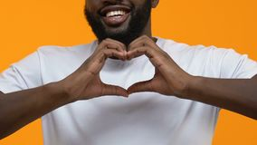 Happy black man in white t-shirt showing heart sign hands, charity gesture, love. Stock footage stock video footage