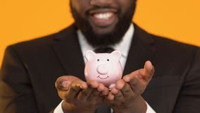 Happy black manager in suit showing piggy bank into camera, savings concept