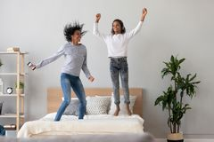Happy black mom and daughter jump on bed listening music stock photo