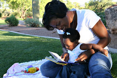 Happy Black Mother & Daughter. African American mother and infant daughter reading a book Royalty Free Stock Images