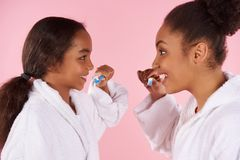 Happy black mother and daughter in dressing gown. Brush teeth. Dental hygiene concept. Isolated on pink background. Studio portrait Royalty Free Stock Photography