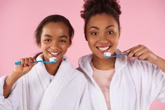 Happy black mother and daughter in dressing gown. Brush teeth. Dental hygiene concept. Isolated on pink background. Studio portrait Stock Images
