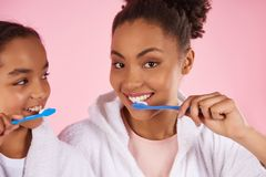 Happy black mother and daughter in dressing gown. Brush teeth. Dental hygiene concept. Isolated on pink background. Studio portrait Royalty Free Stock Image