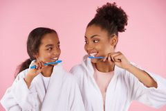 Happy black mother and daughter in dressing gown. Brush teeth. Dental hygiene concept. Isolated on pink background. Studio portrait Royalty Free Stock Photos