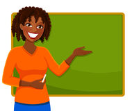 Happy black teacher. Happy teacher standing next to a blackboard Stock Photography