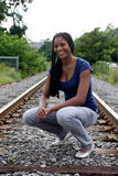 Happy, black teenage girl on railroad tracks Stock Image