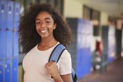 Happy black teenage girl smiling in high school corridor Royalty Free Stock Images