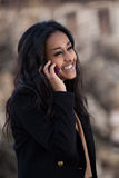 Happy black teenage girl using a mobile phone. Outdoor of a portrait happy young black  teenage girl using a mobile phone Royalty Free Stock Photography