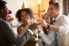Happy black and white friends clinking glasses celebrating party stock photos