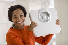 Happy Black woman holding scale. Beautiful African American woman holding scale Royalty Free Stock Image