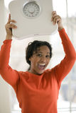 Happy Black woman holding scale Royalty Free Stock Photo