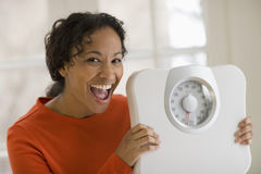 Happy black woman holding scale Royalty Free Stock Photos