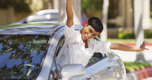 Happy black woman leaning out car window with hands in the air Stock Image