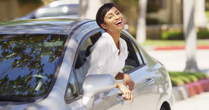 Happy black woman leaning out car window. With hands in the air Royalty Free Stock Photos