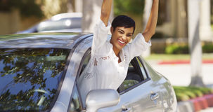 Happy black woman leaning out car window with hands in the air. Smiling Royalty Free Stock Images
