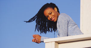 Happy black woman leaning on rail smiling. At camera Stock Image