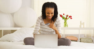 Happy black woman online shopping. On bed Royalty Free Stock Photos