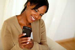 Happy black woman sending a message by cellphone Royalty Free Stock Photography