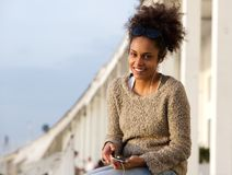 Happy black woman sitting outdoors with mobile phone Royalty Free Stock Photo