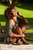 Happy black woman sitting outside with mobile phone Stock Photo