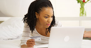 Happy black woman smiling with laptop and credit card Stock Photos
