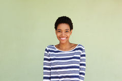Happy black woman in striped shirt smiling by green background. Portrait of happy black woman in striped shirt smiling by green background Royalty Free Stock Photography