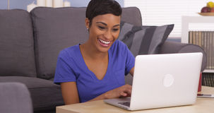 Happy black woman surfing the internet. On laptop Royalty Free Stock Image