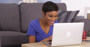 Happy black woman surfing the internet. On laptop Stock Images