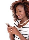 Happy black woman texting. Royalty Free Stock Image