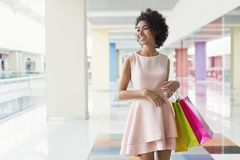 Happy black woman walking in shopping center. Happy black woman walking with coloured shopping bags in shopping center Royalty Free Stock Images